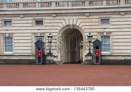 LONDON ENGLAND - OCTOBER 21, 2015: British Royal Guards at the entrance of Buckingham palace. Buckingham Palace is the London residence and administrative headquarters of the reigning monarch of the United Kingdom