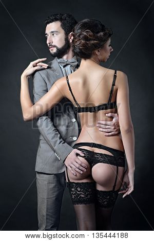 Beautiful lady in panties and bra with guy in suit. Young couple is hugging each other. Portrait of girl in underwear and boy indoors in passionate pose. Beauty woman with attractive lace lingerie
