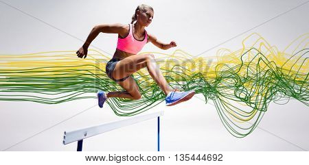 Sporty woman jumping a hurdle against blue design