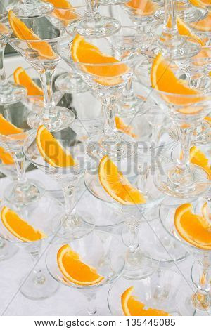 Pyramid of champagne glasses with orange slices