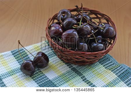 Ripe juicy cherries lies in a small brown wicker basket. The basket stands on a wooden surface next to the towel.