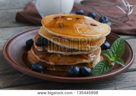 Blueberry pancakes on a plate pour maple syrup