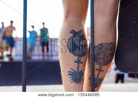 GRODNO, BELARUS - JUN 18: The tattooed legs of one of the participants of Skateboard Challenge 2016 in Grodno, Belarus, June 18, 2016