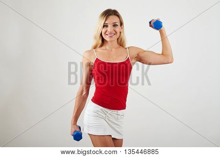 Beautiful athletic girl is holding dumbbells and showing her nicely sculpted muscular body on white background