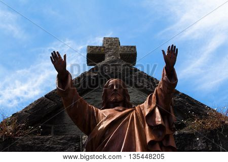 The statue in front of the Saint Rose Church with a cross and cloudy skies in the background in Santa Rosa California.