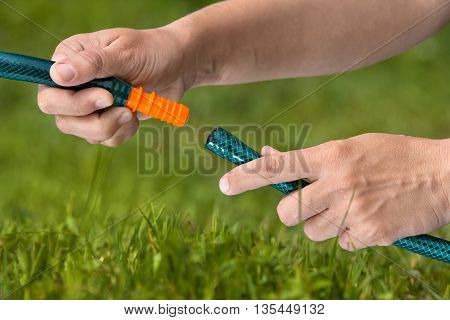 hands connecting hoses for irrigation of lawn or garden closeup
