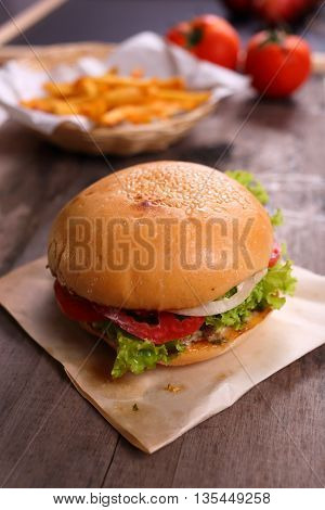 Hamburger with french fries on wooden background