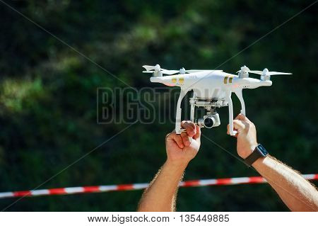 Male hand with drone over head on the background of warning tape
