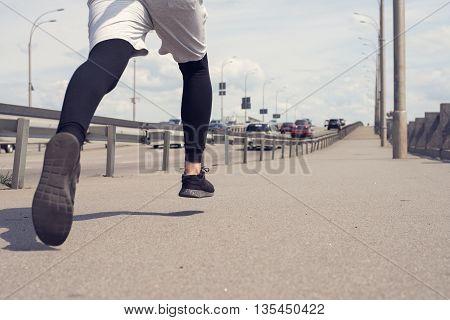 low angle of city runner. closeup of running man