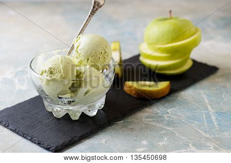 Green refreshing pistachio ice cream in glass bowl selective focus