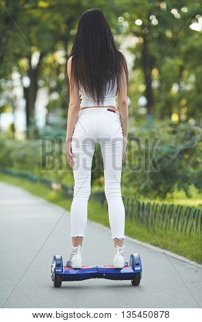 Young sexy fit woman in white riding hoverboard - electrical scooter, personal eco transport, gyro scooter, smart balance wheel
