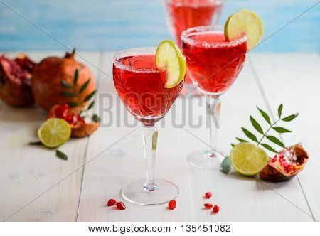 Glasses of garnet juice with lime on white wooden background
