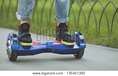 Feet of girl in jeans riding electric mini hover board scooter outdoors in park. Ecological city transportation on battery power.