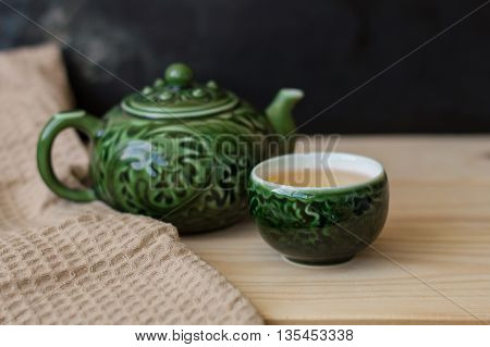 Green tea in a small cup and teapot on wooden background with kitchen towel chinese tea ceremony set