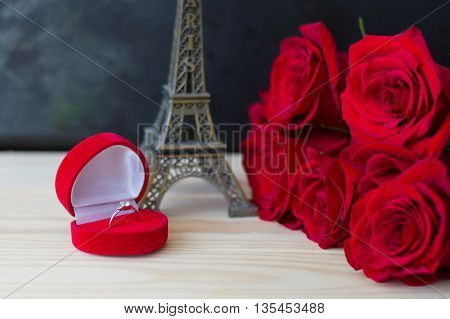 Red roses and an engagement ring in a small red gift box near statuette of Eiffel Tower Valentine's day concept