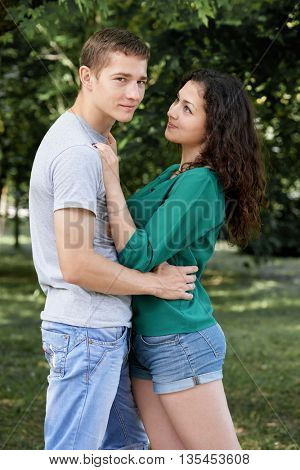 Romantic couple posing in city park, summer season, lovers boy and girl