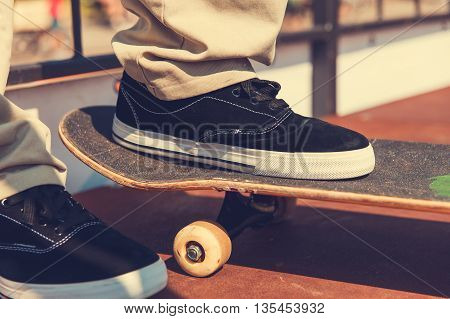 Close-up of skater's leg on a skateboard while preparing for a jump on a skate ramp