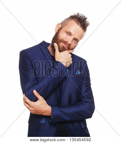 Young bearded man isolated at white background. Portrait of guy with beard thoughtful, pensive, charming and smiling, looking at camera. Boy style, cool hairstyle, trendy hipster in blue suit.