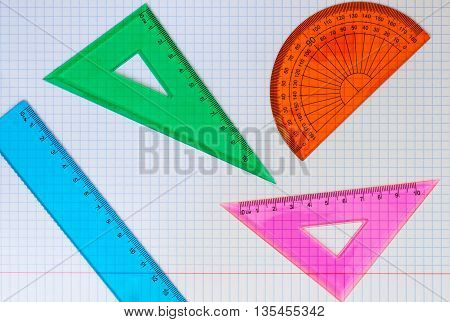 Set of rulers, triangles, and compass for school on a white background of exercise book close-up