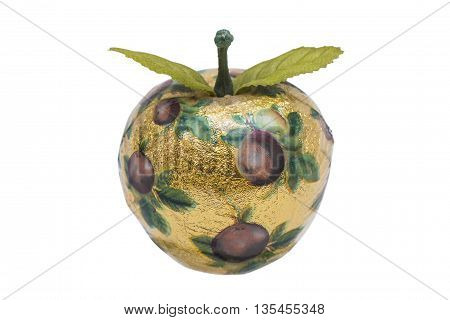 Artificial apple made of wood with gold paper and pattern, with green plastic leaves on isolated white background