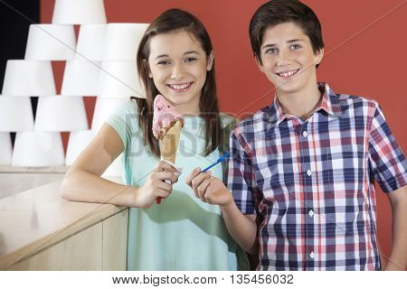 Brother And Sister Holding Spoon And Strawberry Ice Cream