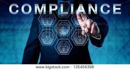 Male corporate auditor is touching the term COMPLIANCE on an interactive virtual control screen. Business challenge metaphor and corporate standard concept for meeting regulatory requirements.