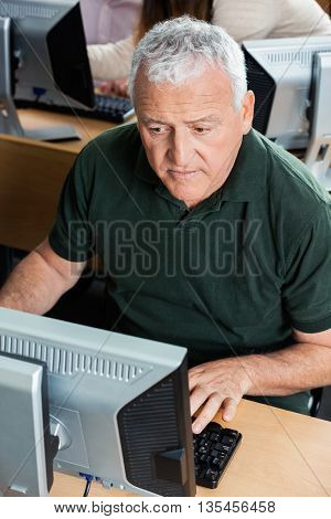 Old Man Using Computer In Classroom