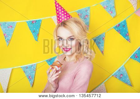 Beautiful smiling young blonde woman with a cake. Celebration and party.Colorful studio portrait with yellow background
