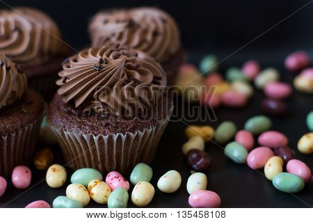 Fresh chocolate cupcakes and colorful jelly sweets on black metal background