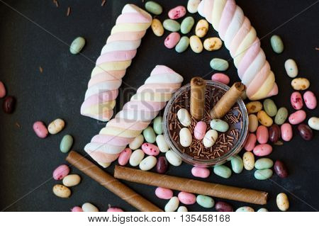 Variety of sweet desserts: marshmallow jelly beans and wafers on black background