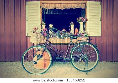 Old bicycle and flowers parked near window of farmhouse at countryside in vintage style