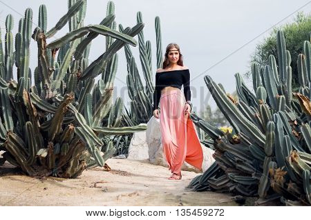 Hippie woman in long pink skirt walking near big cactuses