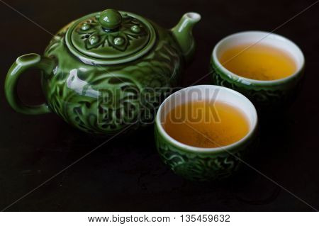 Green tea in two small cups and chinese traditional tea kettle
