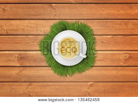 Cup of cappuccino coffee with image of ECO symbol and grass around the cup on wooden surface. Symbols and signs. Eco-friendly planet. Ecologically clean environment. Natural products.
