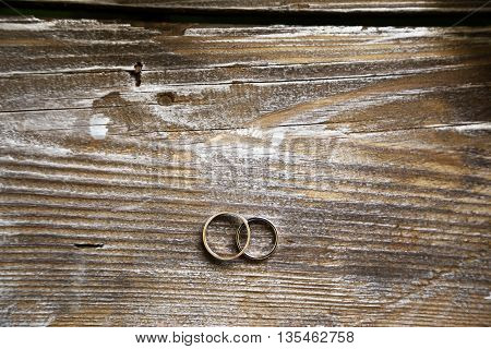 two gold wedding rings on wood table