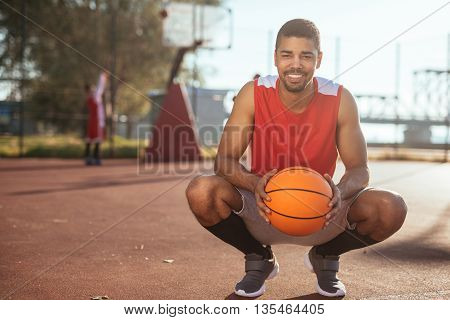 Portrait of handsome african american basketball player holding a ball.