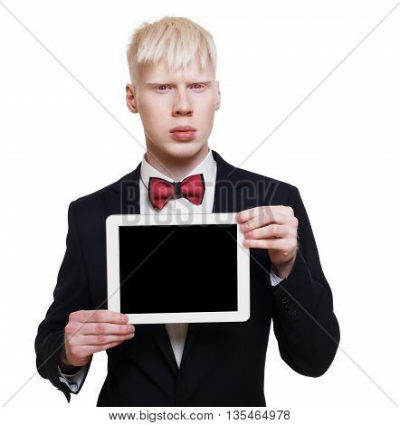 Albino young man portrait with tablet. Blond pale guy in suit with red bow tie isolated at white background. Stylish male person shows computer device with copy space at black screen