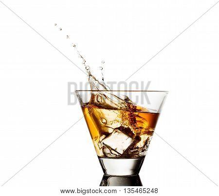 splash of whiskey with ice osolated on white.