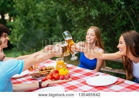 Group of friends enjoying lunch and toasting beer.