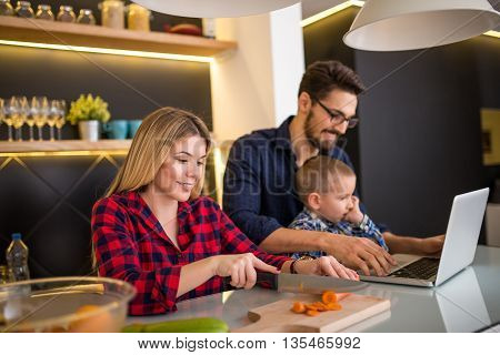 Mom preparing food together at home while dad and son are having fun.