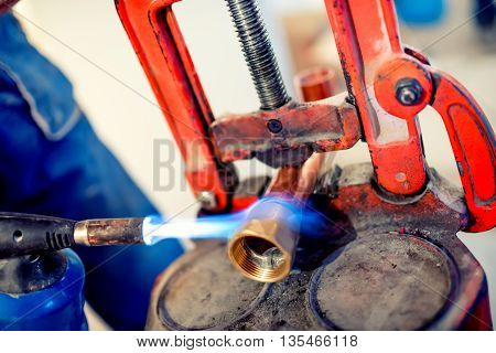 Plumber Welding Copper And Fittings With Blowtorch