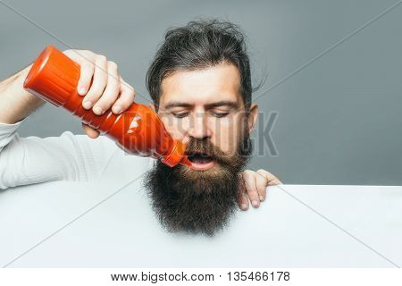 handsome bearded man with long lush beard and moustache on serious face holding red plastic ketchup bottle with paper sheet on grey background