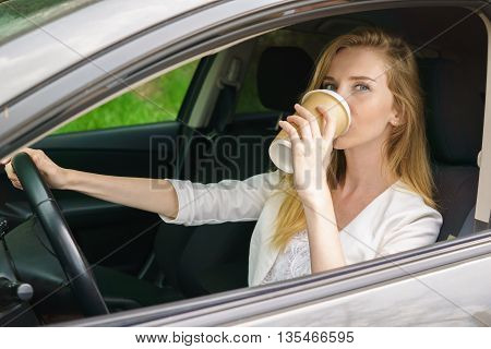 Smiling young bautiful woman sitting in car