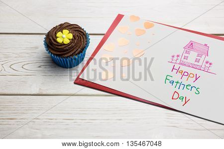 Word happy fathers day and drawn pink house against delicious cupcakes on a table