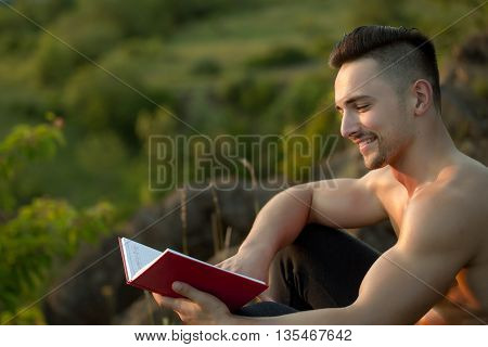 Smiling Muscular Man With Book Outdoor