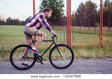 Young Hipster Man Riding A Bike