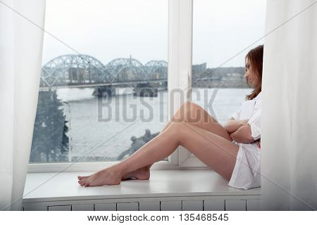 thoughtful woman with a book sitting near window