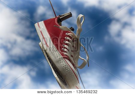 pair of red sneakers hanging on a clothespin on the background of the sky with clouds