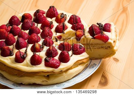 round fresh strawberry pie or cake with cream and chocolate icing on white plate on wooden table background