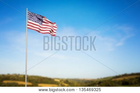 American flag waving on pole against blue sky over fields